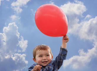 Ein Kind hält roten Luftballon vor blauem Himmel in die Höhe