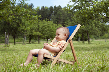 Baby or  toddler child relaxing in a garden.