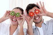 Funny couple covering their eyes with fruit