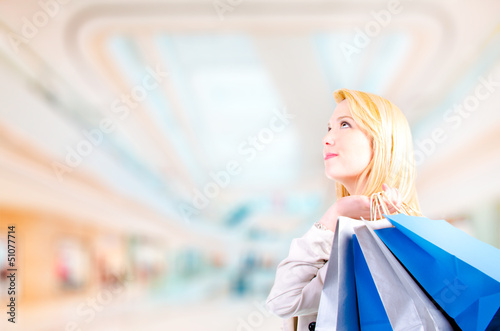 Young woman holding shopping bags looking upwards at copyspace