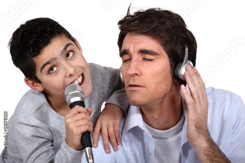 Father and son singing into a microphone