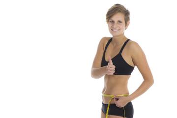 Junge sportliche Frau mit Maßband in Unterwäsche
