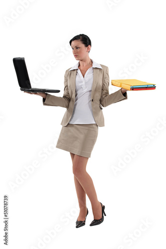 Woman carrying laptop and folders