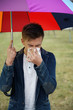 Junger Mann schneuzt wegen Schnupfen bei Erkältung