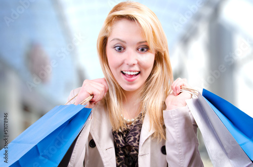 Beautiful woman with shopping bags looking down surprised
