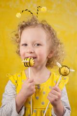 Girl tasting a bee cake pop