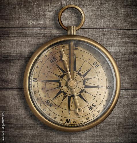 Leinwandbild Motiv old brass compass on wood table top view