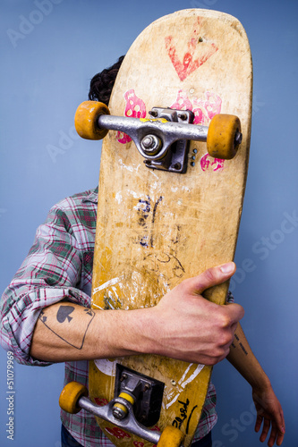 Skater hiding behind his skateboard