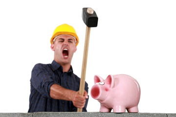 craftsman breaking a pig bank with a hammer