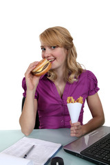 Woman eating a cheeseburger and fries at her desk