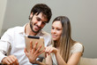 Couple sitting on sofa with electronic tablet