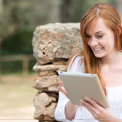 frau mit tablet-pc in der natur