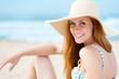 lächelnde frau mit sonnenhut am strand
