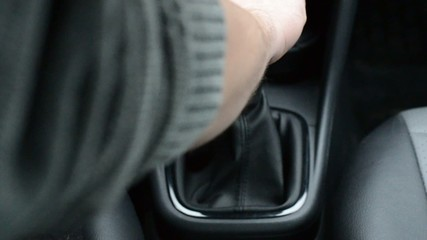 driving a car, with hand on the gearshift knob