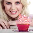 Junge hübsche Frau mit Cupcake lächelt vergnügt
