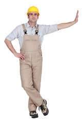 A man in overalls with his hand on a wall.