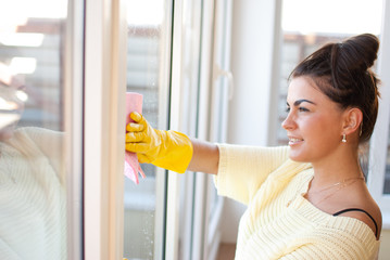 Young woman clean windows