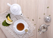 teapot with cup of tea, tea bag, lemon, sugar,