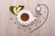 wooden table with cup of tea, watch and lemon