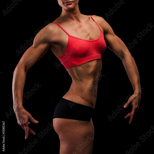 Muscular strong woman on a black background