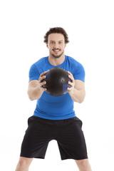 Sportlicher Mann steht angriffslustig mit einem Ball in Händen