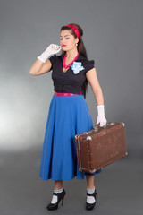 young attractive pinup woman with retro suitcase