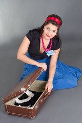 young attractive pinup girl packing retro suitcase