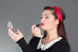 pinup woman putting red lipstick