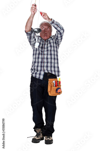Electrocuted man fixing a light fixture