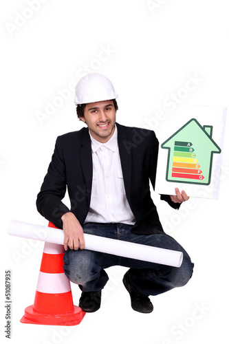 businessman holding a blueprint and an energy consumption label