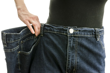 Closeup of a slim woman waist in oversized pants