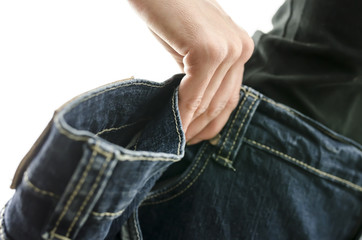 Detail of woman skinny waist in too large old jeans