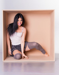 Happy woman model trapped in box concept
