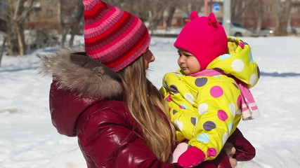 Pretty mother in winter clothes holding her daughter at winter