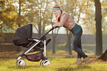 Young mother with a baby carriage walking in a park