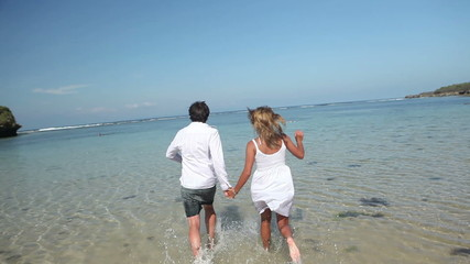 couple holding by hands and running together on coastline