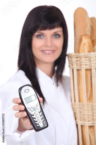 Female bakery worker with mobile telephone