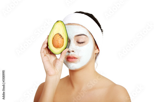 Young woman holding avocado