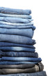 Many jeans stacked in a pile isolated on white