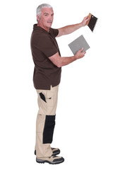 Man holding a tile and a spatula