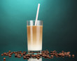 Cold coffee with ice in glass on color background
