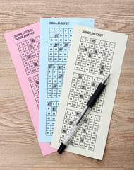 Lottery tickets and pen, on wooden background