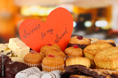 Sweet cookies with valentine card on table in cafe