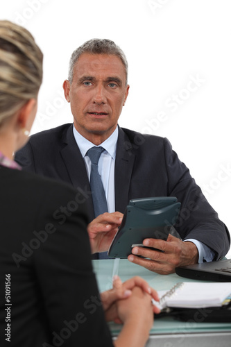 Businessman with calculator talking to his collaborator