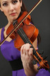 Beautiful young girl with violin on grey background