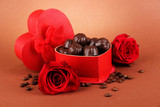 Chocolate candies in gift box, on brown background