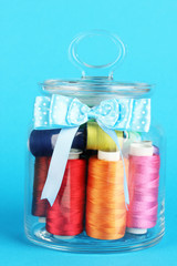 Glass jar containing various colored thread on blue background