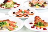 Small portions of food on big white plates close up