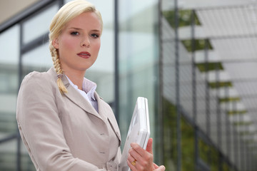 Businesswoman holding computer outside glass building