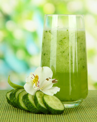 Glass of cucumber juice, on bamboo mat, on green background
